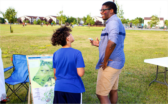 A WeDesign student participant and Kene Okigbo, communication intern at Reach Partners, discuss natural play at World Garden Commons Party in the Park